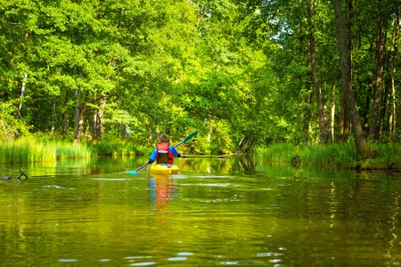 Kayaking by wild river in forest in poland (Omulew river near Nidzica). Summer recreation. Stock Photo