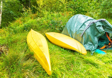 Camping in forest, tent and kayaks in green summer forest. Polish countryside. Stock Photo