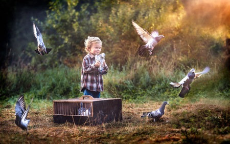 Boy playing outdoor in autumn or spring scenery with flying pigeons.
