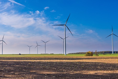 Spring or autumnal landscape with windmills on fields.