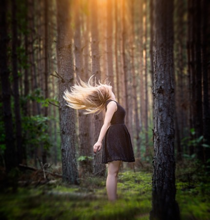 loose hair: Portrait of young blonde girl with loose hair in european forest at windy day.