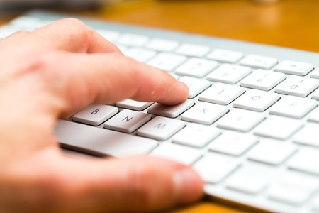 Close up of white wireless aluminum keyboard photographed with shallow depth of field. Stock Photo