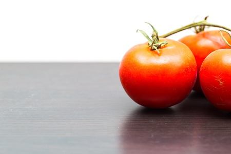 Twig of old tomatoes lying on dark table. Ripe red tomatoes