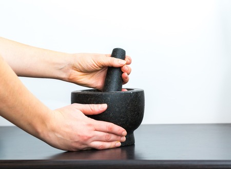 granite kitchen: Granite mortar standing on kitchen table and woman hands. Kitchen tool in close up.