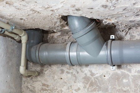 Sewer pipes in home basement. System of gray sanitary pipes in old house. Stok Fotoğraf - 66292547