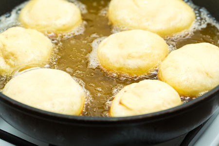Donuts frying in deep fat. Preparation of traditional donuts Standard-Bild