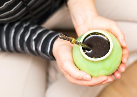 yerba mate: Mujer irreconocible yerba mate en mano de la taza de cerámica.