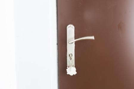 doorhandle: Close up of doorhandle, key and door in home. Brown doors and steel doorhandle.