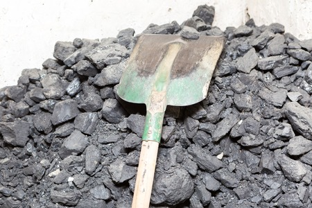 Black coal lying and shovel on a pile in house basement. Fuel material. Standard-Bild