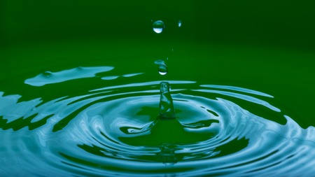 to trickle: Close up of splashing droplet and water surface. Abstract background.