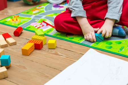 wooden blocks: Small boy playing with wooden blocks on floor. Baby toy and child.