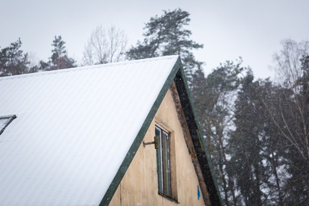 wintertime: House roof with snow. Wintertime building in close up. Stock Photo