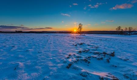 Beautiful winter sunset on fields landscape. Colorful landscape of sunset in winter. Stock Photo