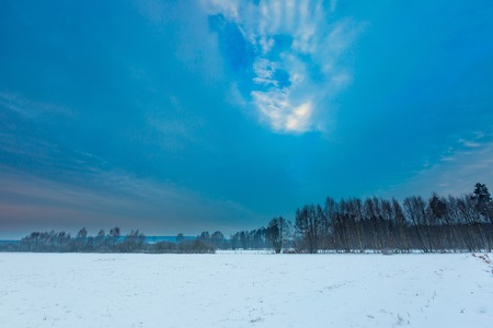 Winter sunrise on meadows. Polish typical winter rural landscape. Calm day beginning.  Stock Photo