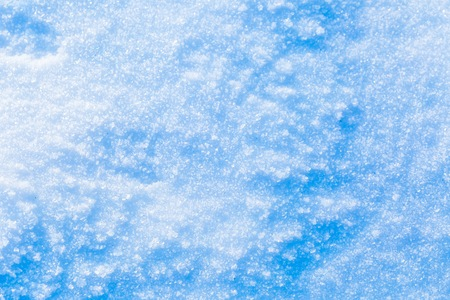 Snow background in close up. Surface of fresh winter snow in sunset ligh.