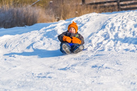 Happy little caucasian boy downhill on plastic slider or sledge. Winter child outdoor activity.