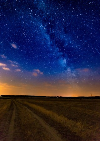 Milky way over stubble field and rural sandy road. Night landscape with starry sky and stubble field.