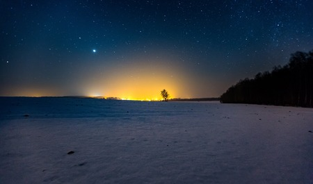 Milky way and starry sky over winter landscape and distant village. Night sky astrophotography background.