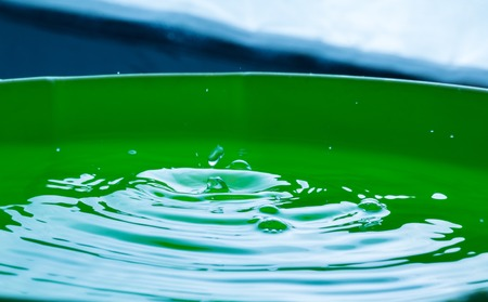 massage symbol: Close up of splashing droplet and water surface. Abstract background.
