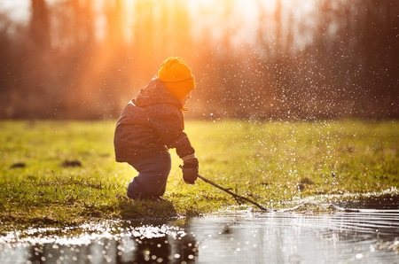 Little boy playing in puddle at springtime. Happy childhood Imagens