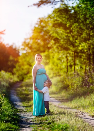 Pregnant woman outdoor portrait. Beautiful caucasian pregnant woman and shes older son Archivio Fotografico