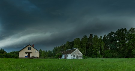 Scarry dark storm clouds over forest and house. Very dangerous weather.