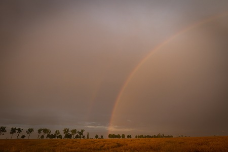 Beautiful rainbow over fields. Natural landscape with rainbow. Banco de Imagens