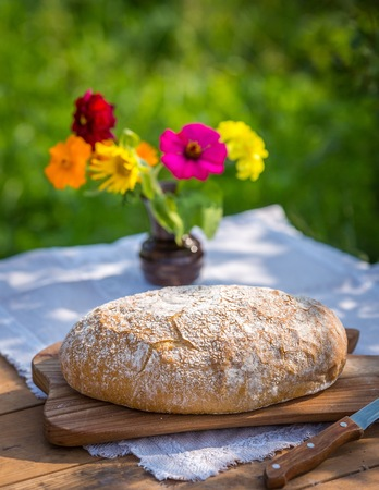 black textured background: Still life with organic bread. Tasty fresh baked bread photographed on table in garden