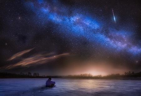 nuit paysage d & # 39 ; astrophotographie avec l & # 39 ; homme assis sur la neige et regarder des