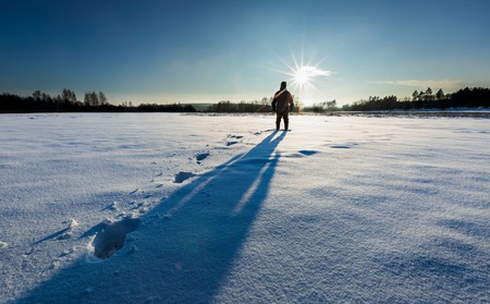 Man silhouette in tranquil winter landscape. Surreal landscape with human,
