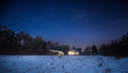 Winter night landscape with house near forest. Calm night in polish countryside