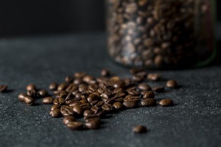 Glass jar with coffee beans on dark background. Close up of coffee.