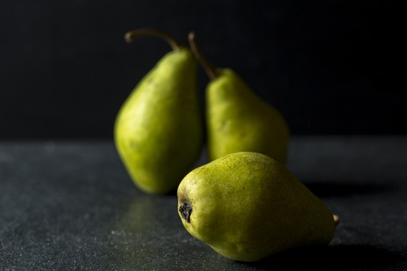 Green pears lying on dark background. Fresh fruits on dark backdrop.