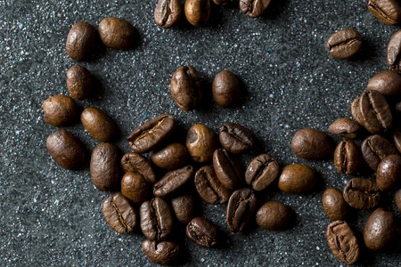 Coffee beans in close up lying on dark background. Coffee background.