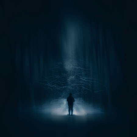 Surreal night forest landscape with alone strange man with flashlight. Horror scene. Stok Fotoğraf
