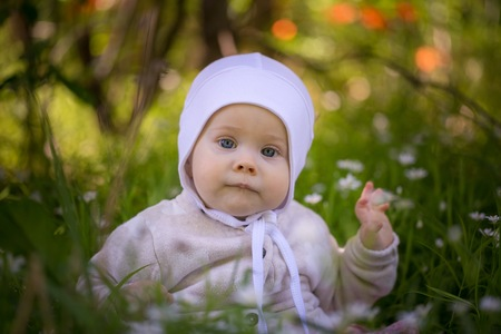 Small caucasian baby girl sitting in grass in forest. Beautiful infant baby girl portrait  in nature. Archivio Fotografico
