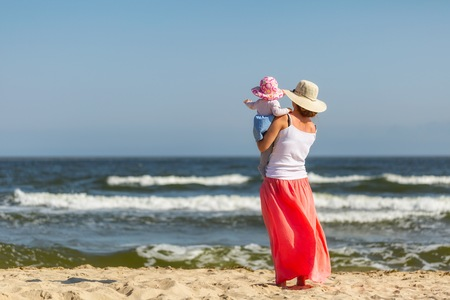 Mother and little baby girl on sea shore. Beautiful family photography. Stock Photo