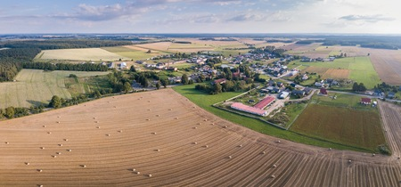 Aerial: Fields near village, stubble with straw bales at late summer. Drone landscape.