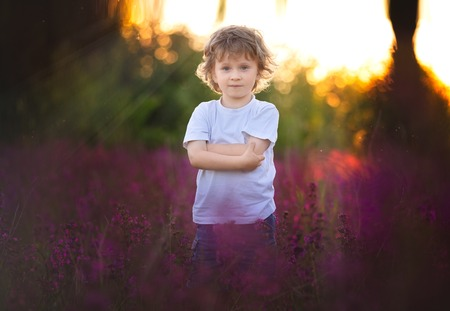 Handscome boy standing in red wildflowers. Serious face and curly hair. 写真素材
