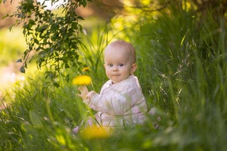Piccola neonata caucasica che si siede nell'erba nella foresta. Bello ritratto infantile della neonata in natura.
