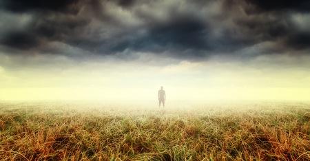 Silhouette of strange man standing in distant fog. Spooky, surreal landscape.