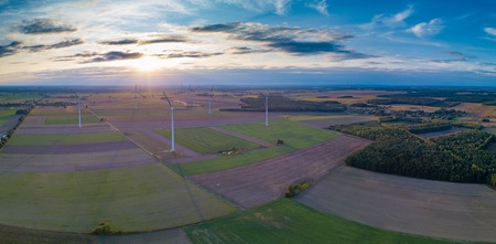 Aerial: FIelds and windmills in sunset light. Drone view