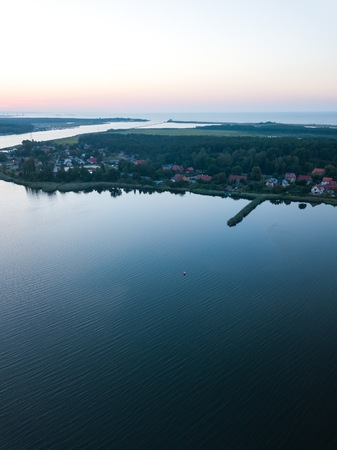 Beautiful sunset over estuary of Vistula river in Gdansk. Summer sunset over sea and river and small village. Stock Photo