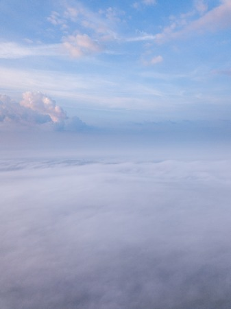 Beautiful foggy sunrise landscape from drone. Magical sunrise over the clouds.