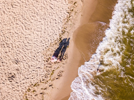 Baltic beach from above with people . Drone photography with sandy shore and waves of sea.