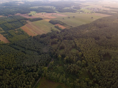 Beautfiful summer sunset over foggy european forest. Drone photography