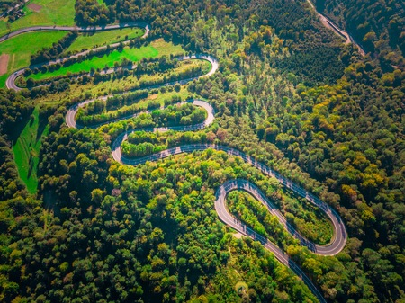 Serpentine road in Bieszczady mountains photographed from drone. Curves on asphalt road, top down drone landscape.