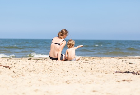 Mother and son spending time on sea shore at sunny and warm summer day. Family photo.