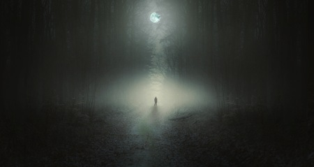 Surreal horror scene with alone strange man in dark night forest. Dreamy landscape. 版權商用圖片
