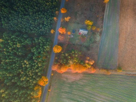 Beautiful top down aerial landscape with farm buildings near autumnal forest.